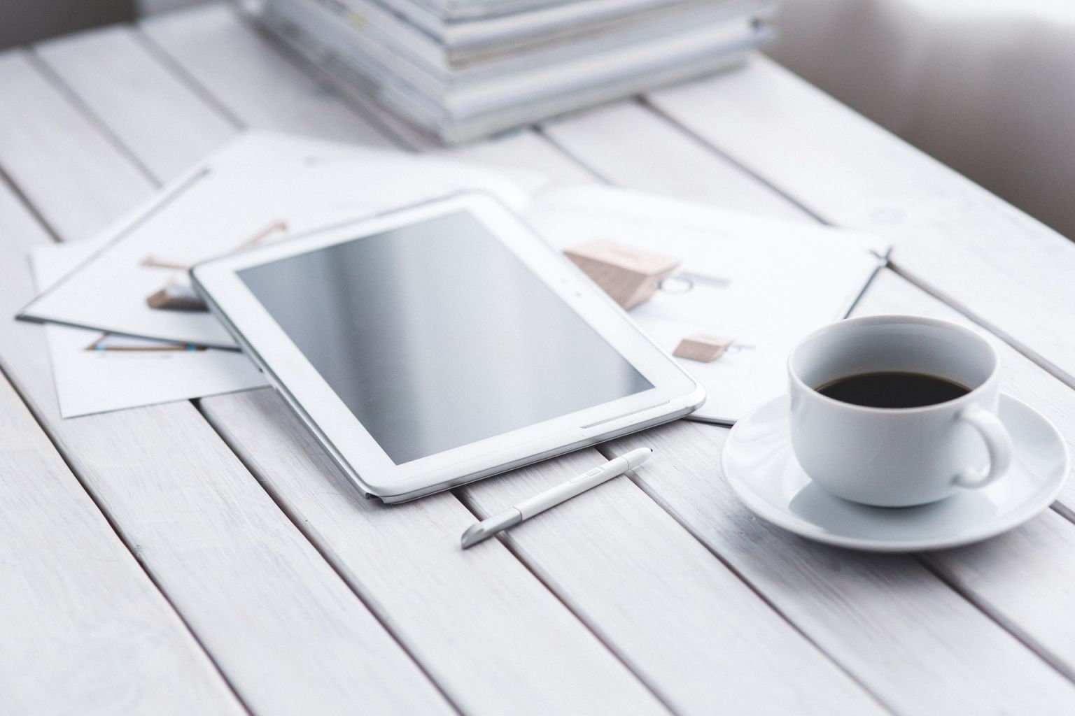 Entrepreneur's or business manager's desk with a white tablet and stylus next to a coffee cup and a few documents.
