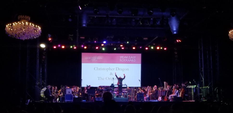 The Colorado Symphony with the conductor, Christopher Dragon, with his arms raised as the musicians get ready to play for the Colorado Symphony Ball