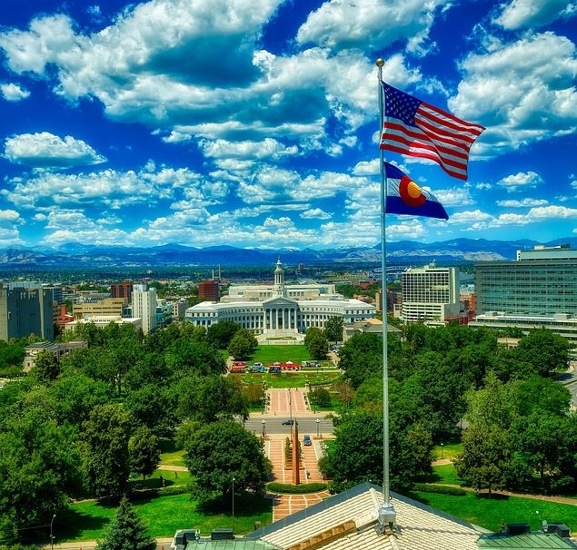 Looking out at the Denver City and County Building from the Colorado State Capitol building in downtown Denver, Colorado on a beautiful afternoon with the American and Colorado state flags high in the bright sky under white fluffy clouds with the Rocky mountains off in the distance.