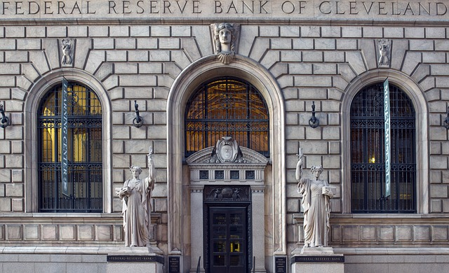 Image of the front of the Federal Reserve Bank of Cleveland - a beautiful stone building with gray statutes on each side of a black door.