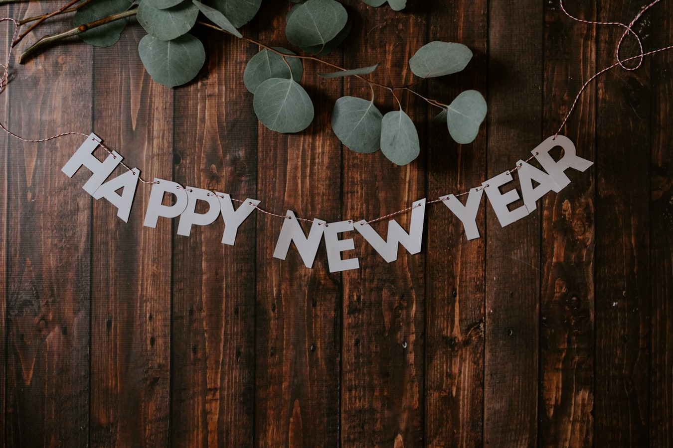 The words 'Happy New Year' are hung in a silver banner across a dark wooden table with a bit of greenery above