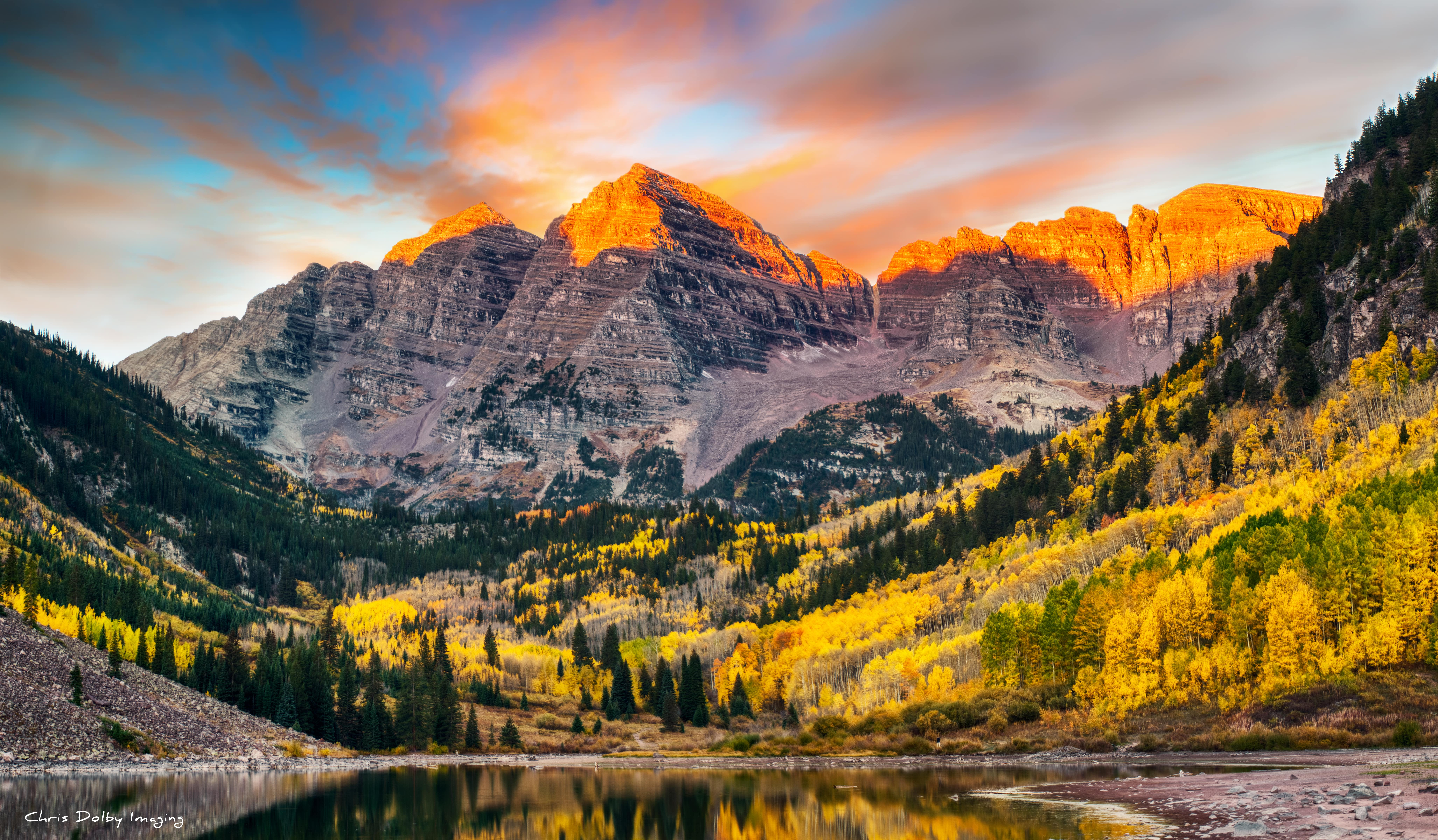 The majestic maroon bells at sunrise, the sky lit up with pinks and blues.