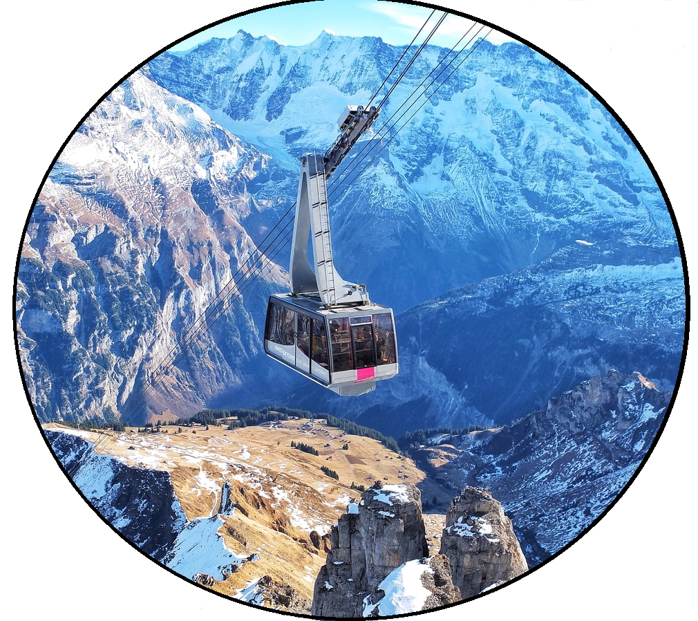 A large glass aerial tram ascends to the top of snow-covered, dazzling mountains on a clear day