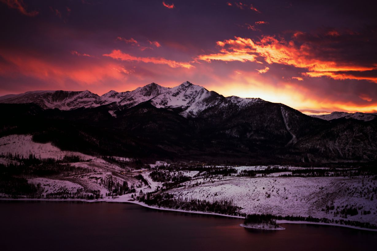 The sky is ablaze at sunset over the snowy Rocky Mountains in Colorado, towering above a still Alpine lake.