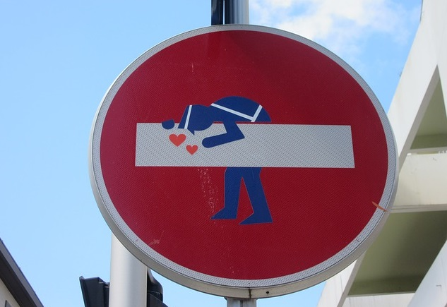 a red sign with a police officer or other offical in a blue suit bent over and kissing a horizontal solid bar with two small pink hearts in front of the bar.
