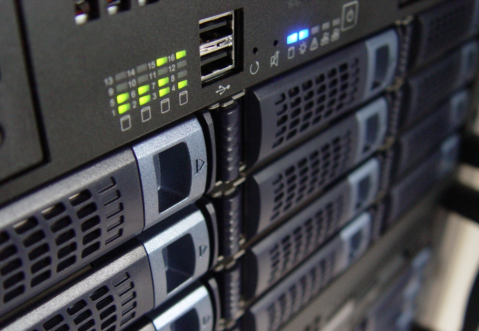 a close-up image of the front of a black server panel with hot-swappable hard drives, the blue and green system lights indicate the system is in great shape.